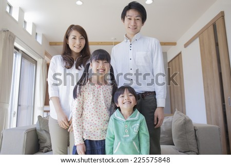 Family standing in front of the sofa - stock photo