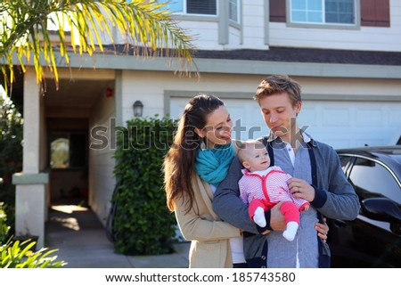 Family standing in front of their home - stock photo