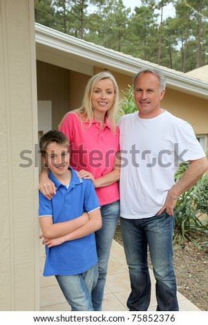 Family standing in front of their house - stock photo