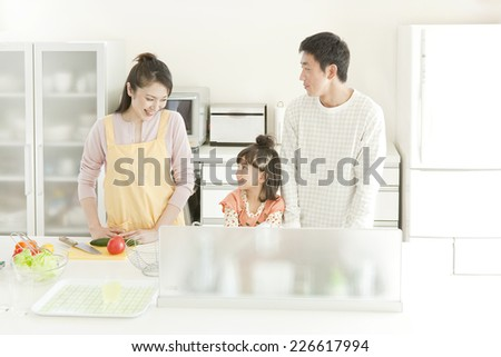 Family standing in the kitchen - stock photo