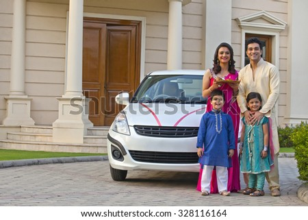 Family standing next to new car