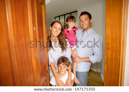 Family standing on the entrance door of new home - stock photo