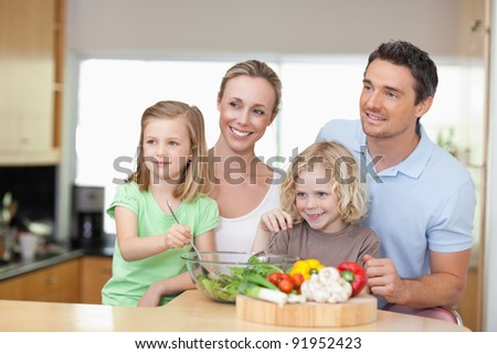 Family standing together next to salad