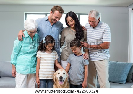 Family standing together with dog in living room - stock photo