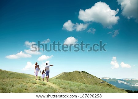 Family stay on the top of mountain, looking on the beautiful view. - stock photo