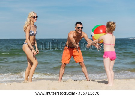 family, summer vacation, adoption and people concept - close up of happy man, woman and little girl playing with inflatable ball on beach - stock photo