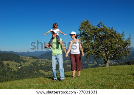 Family summer vacation in mountains. Active happy parents with kid having fun in travel
