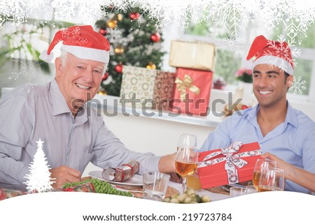 Family swapping christmas presents against fir tree forest and snowflakes - stock photo