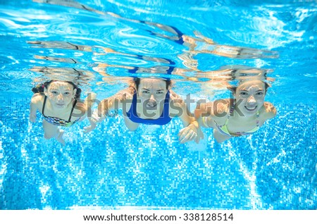 Family swim in pool underwater, happy active mother and children have fun in water, kids sport on family vacation