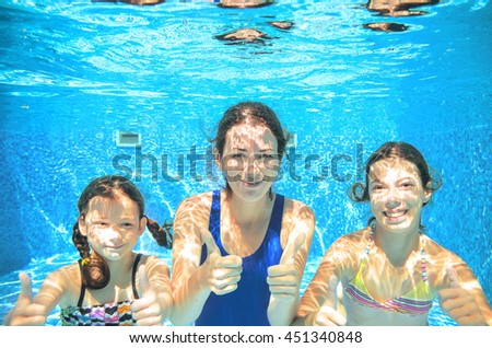 Family swims in pool under water, happy active mother and children have fun underwater, kids sport on vacation  - stock photo