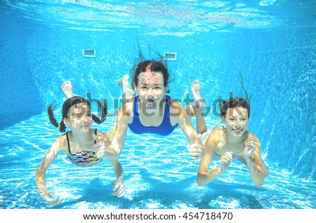 Family swims in pool underwater, happy active mother and children have fun, kids sport on vacation  - stock photo