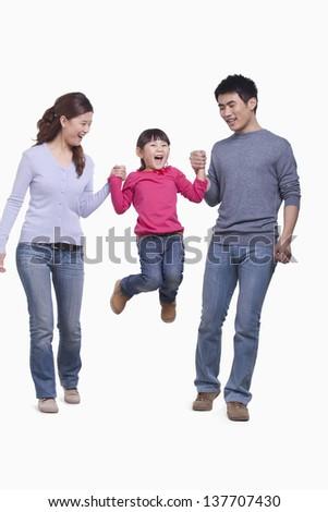 Family swinging child in mid-air, studio shot - stock photo
