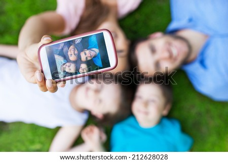 Family taking picture of themselves with smartphone - stock photo