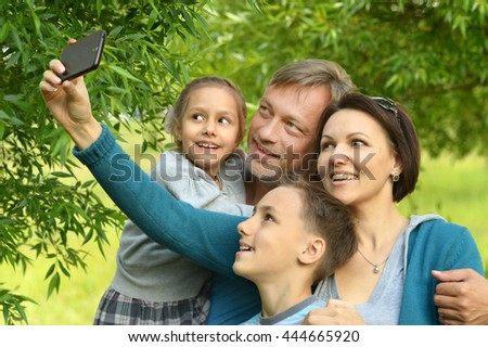 family taking selfie in park