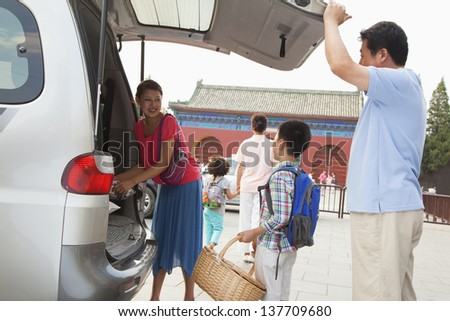 Family taking stuff out from the car, preparing for picnic - stock photo