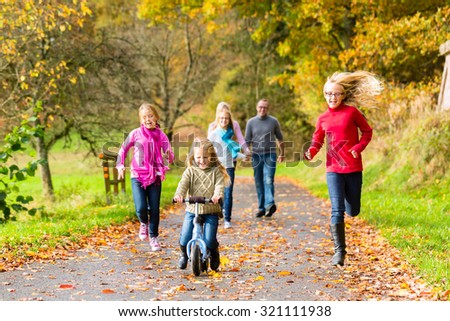 Family taking walk in autumn fall forest