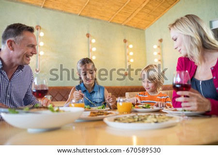 Family talking while having dinner at restaurant