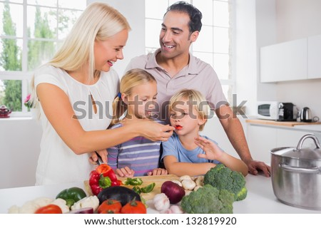 Family tasting vegetables together - stock photo