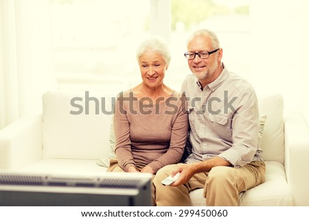 family, technology, age and people concept - happy senior couple watching tv at home - stock photo