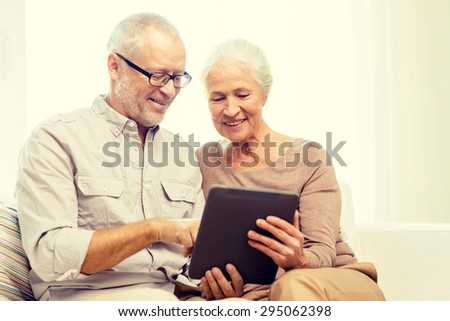 family, technology, age and people concept - happy senior couple with tablet pc computer at home - stock photo
