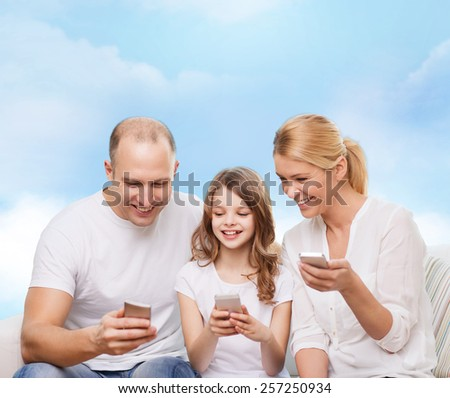 family, technology and people - smiling mother, father and little girl with smartphones over blue sky background - stock photo