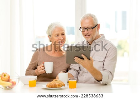 family, technology, food, drinks and people concept - happy senior couple with tablet pc computer having breakfast at home
