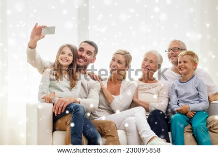 family, technology, generation and people concept - happy family sitting on couch and making selfie with smartphone at home - stock photo