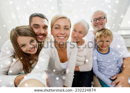 family, technology, generation and people concept - happy family sitting on couch and taking self portrait with camera or smartphone at home - stock photo
