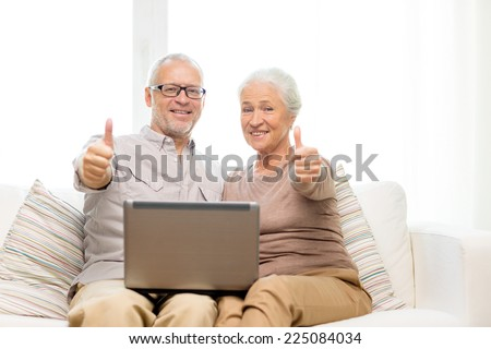 family, technology, gesture, age and people concept - happy senior couple with laptop computer showing thumbs up at home - stock photo
