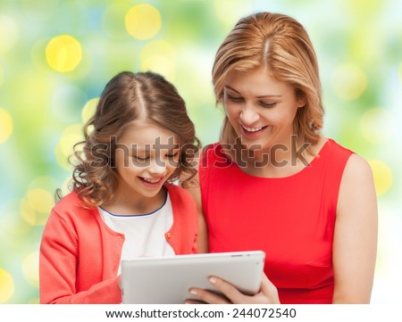 family, technology, people and christmas holidays concept - happy mother and daughter with tablet pc computer over green lights background - stock photo