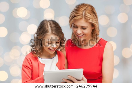 family, technology, people and christmas holidays concept - happy mother and daughter with tablet pc computer over lights background - stock photo