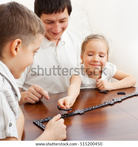 Family that plays dominoes. Father playing with children at home