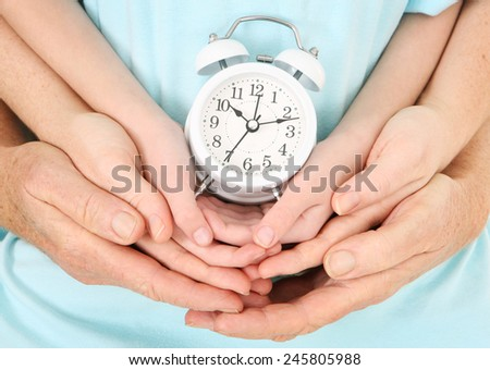 Family time - Father, Mother, and Child holding an alarm clock - stock photo