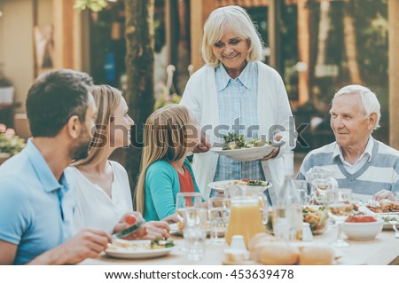 Family time. Happy family of five people enjoying meal together while sitting at the dining table outdoors - stock photo