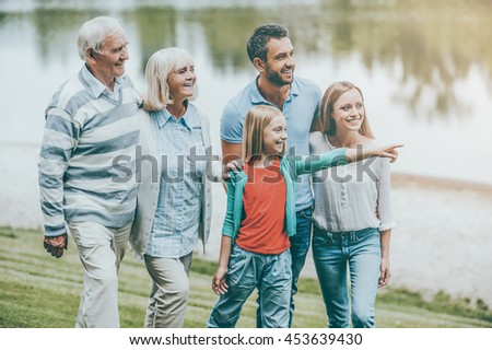 Family time. Happy young family walking outdoors together while little girl pointing away and smiling - stock photo