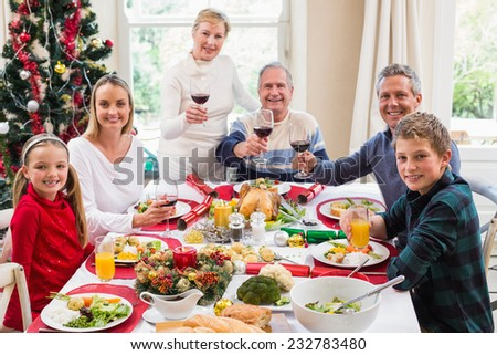Family toasting at camera with red wine at home in the living room