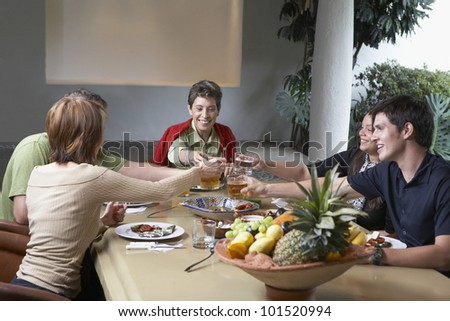 Family toasting at dinner table - stock photo