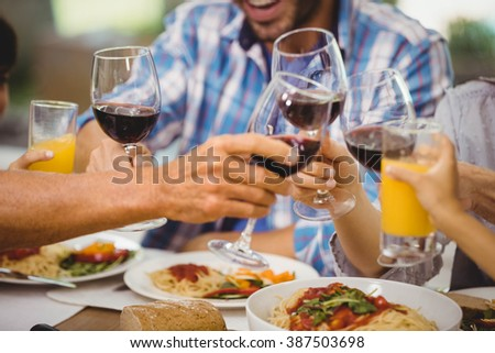 Family toasting glasses of wine on dining table while having a meal