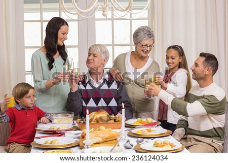 Family toasting with champagne in a christmas dinner at home in the living room - stock photo