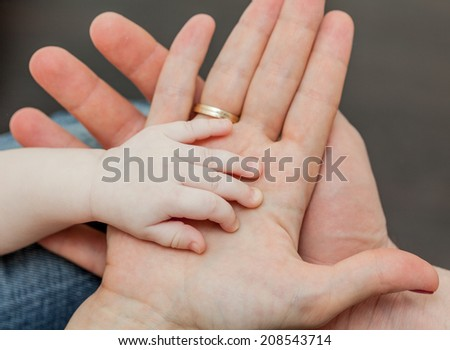 Family together. Father and mother holding child's hand - stock photo
