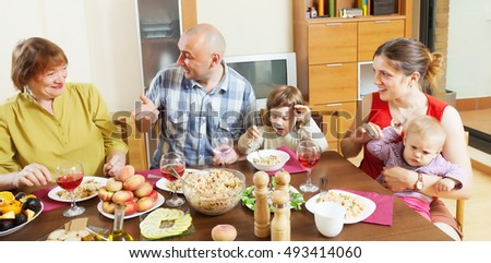 family together over dining table at home interior