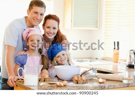 Family together with baking ingredients behind the kitchen counter