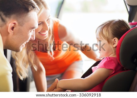 family, transport, safety, road trip and people concept - happy parents talking to little girl in baby car seat - stock photo