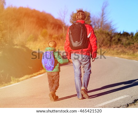 family travel - father and son with backpacks walk on the road