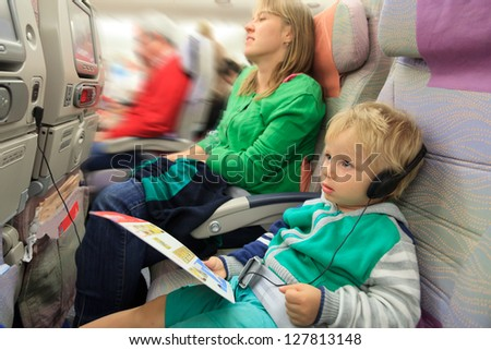 family travel - mother and little boy with headset in flight - stock photo