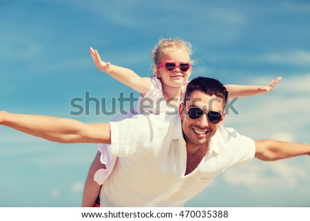 family, travel, vacation, adoption and people concept - happy man and little girl in sunglasses having fun over blue sky background