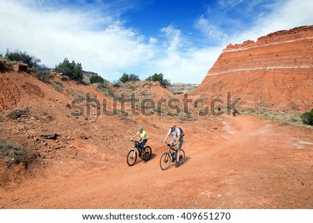 Family traveling by bike along the trail.. Palo Duro Canyon State Park, Texas, US - stock photo