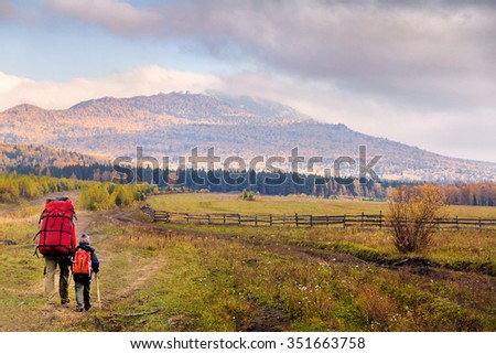 Family traveling on the road among the mountains, forests and fields - stock photo