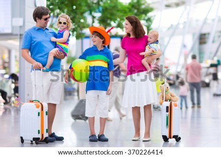 Family traveling with kids. Parents with children at international airport with luggage. Mother and father hold baby, toddler girl and boy flying by airplane. Travel with child for summer vacation. - stock photo