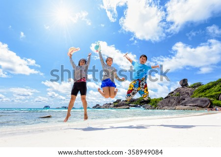 Family travels on vacation jumping with happy on beach near the sea under the sun blue sky and clouds of summer at Koh Similan Island in Mu Ko Similan National Park, Phang Nga province, Thailand - stock photo